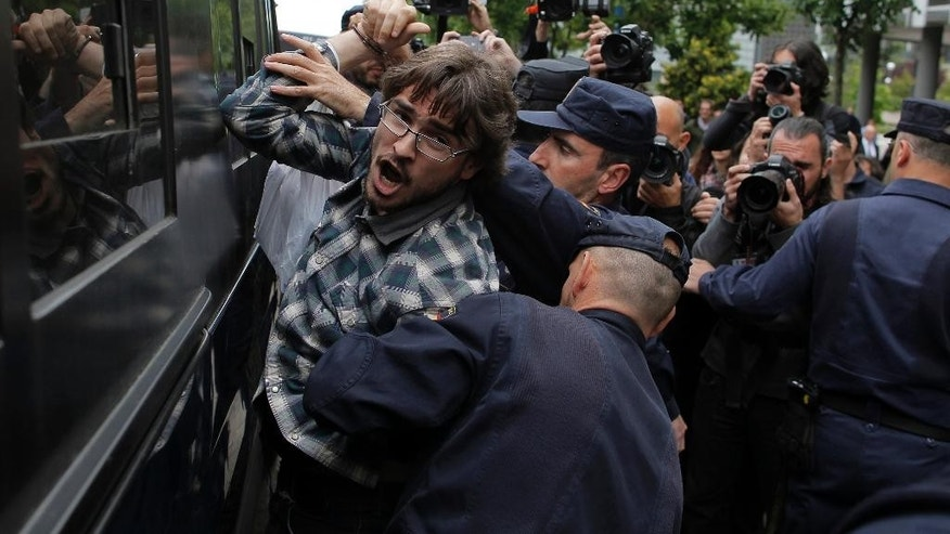 "FILE - In this May 29, 2013  file photo police arrest a protestor after he distributes flyers during a demonstration to stop evictions outside SAREB bank as photographers take pictures in Madrid, Spain. The wide-ranging public security law dubbed ""Gag Law"" has a clause specifying that people can be fined as much as 30,000 euros ($33,000) for ""unauthorized use"" of images of working police that could endanger their security or hinder their ability to successfully complete police operations. (AP Photo/Andres Kudacki, FILE)"