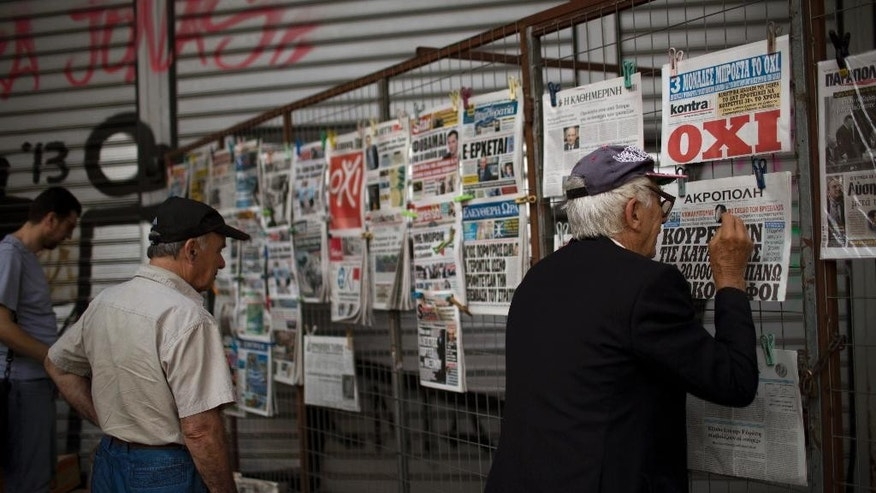 "Men, one of them using a magnifying glass, look at newspapers displayed at a news stand in central Athens, Friday, July 3, 2015. Rival campaigns in Greece's bailout referendum end Friday, with rallies planned in Athens for ""Yes"" and ""No"" supporters - at the same time. (AP Photo/Emilio Morenatti)"