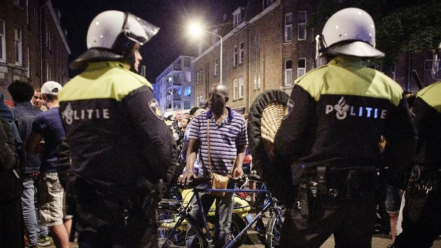 Dutch riot police clash with protesters at Schilderswijk district in The Hague, Netherlands, in the early hours of Friday, July 3, 2015. Dutch police have detained some 200 people for ignoring a ban on public assembly imposed in a neighborhood hit by days of late-night rioting following the death in police custody of a man arrested at a music festival. (AP Photo/Phil Nijhuis)
