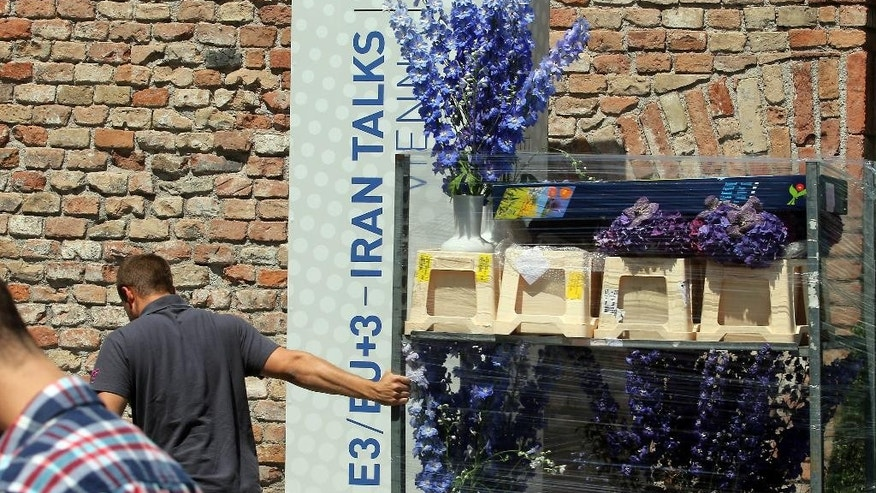 A worker pulls a trolley with flowers out of Palais Coburg where closed-door nuclear talks with Iran take place in Vienna, Austria, Friday, July 3, 2015. (AP Photo/Ronald Zak)