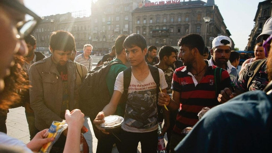 "FILE - In this Thursday, July 2, 2015 file photo migrants receive food and beverage from members of a Facebook organized group at the Keleti Railway Station in Budapest, Hungary. The U.N. refugee agency says in an open letter published on Friday, July 4, 2015, changes to Hungary's asylum system being rushed through parliament and the government's plan to build a fence on the border with Serbia could have ""fatal consequences"" for refugees fleeing war. (Zoltan Balogh/MTI via AP)"