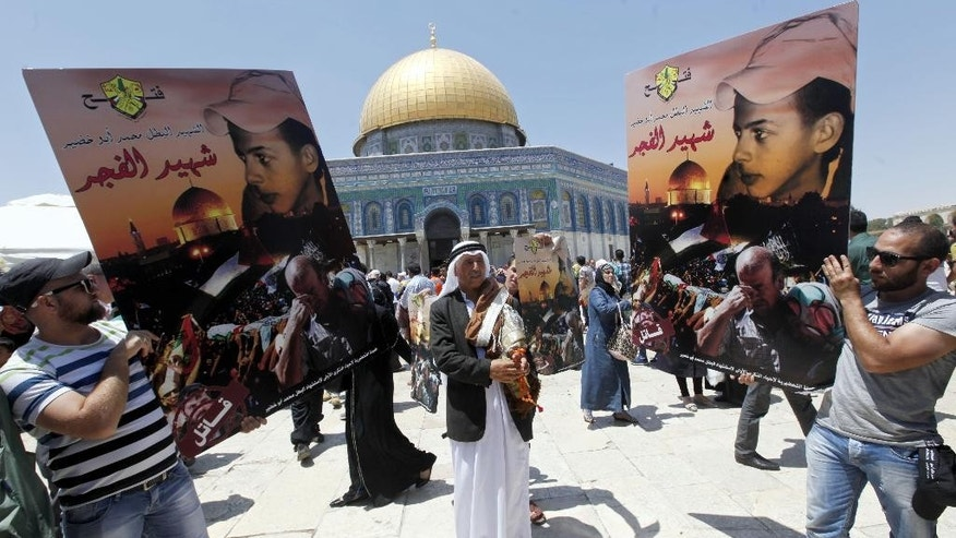"Palestinian men hold signs as they protest next to the Dome of the Rock Mosque in the Al Aqsa Mosque compound, on the third Friday of the Muslim holy month of Ramadan, in Jerusalem's old city, Friday, July 3, 2015. Arabic on sign reads: ""the martyr and hero Mohammed Abu Khdeir - The martyr of dawn."" Abu Khdeir was abducted and murdered by Israeli extremists last year in a revenge attack after Palestinian militants abducted and murdered three Israeli teenagers weeks before. The murders were part of a series of events that sparked a 50-day war between Palestinian militants in Gaza and Israel. (AP Photo/Mahmoud Illean)"