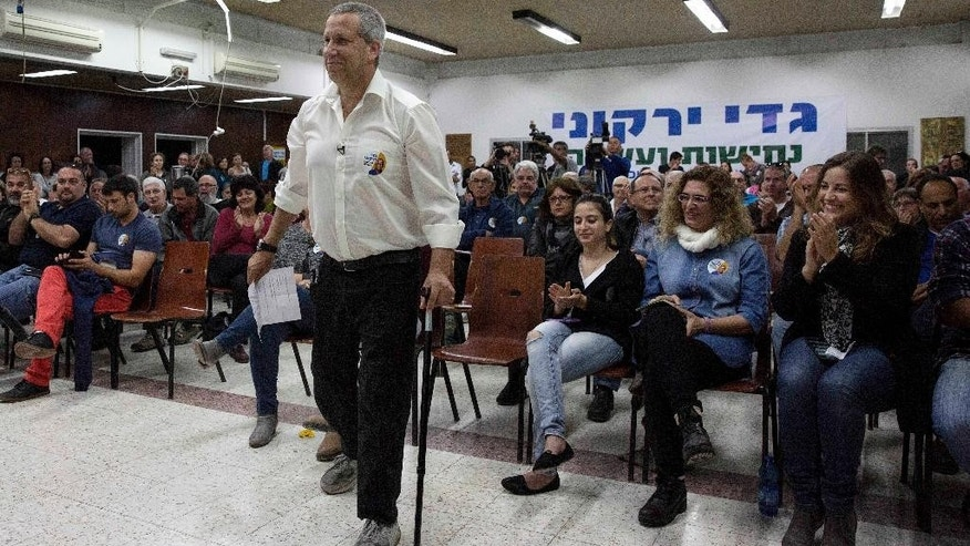In this photo taken, Tuesday, April 14, 2015, Gadi Yarkoni stands during a meeting in the southern Israeli Kibbutz of Nirim. On the last day of the Gaza war last summer, Yarkoni lost both his legs and two of his closest friends when a mortar landed near the men as they were repairing an electricity line in their kibbutz. Nearly a year later, Yarkoni is literally back on his feet _ thanks to prosthetics _ as the newly elected head of the Eshkol Regional Council and helping rebuild Israel's hardest hit region of the war. (AP Photo/Tsafrir Abayov)