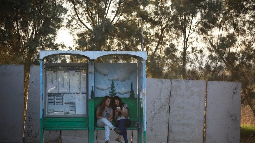 In this Tuesday, June 30, 2015. photo, Israeli girls wait for transportation in a bus stop protected with concrete blocks near the southern Israeli town of Sderot, next to the Israel-Gaza border.  A year after the Gaza war, the community in southern Israel, long battered by rockets from the Hamas-run territory next door, has slowly recovered and is even seeing a quiet boom. (AP Photo/Oded Balilty)