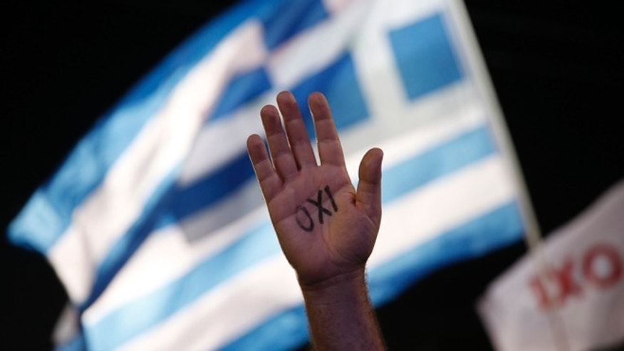 July 3, 2015: A demonstrator rises his hand reading the word ''No'' as a Greek flag waves during a rally organized by supporters of the No vote in Athens.