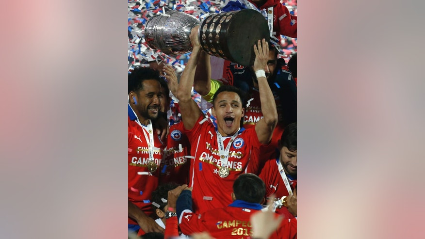Chile's Alexis Sanchez lifts the trophy after winning the Copa America final soccer match against Argentina at the National Stadium in Santiago, Chile, Saturday, July 4, 2015. Chile defeated Argentina 4-1 in a penalty shoot out after the game ended in a 0-0 draw. (AP Photo/Luis Hidalgo)
