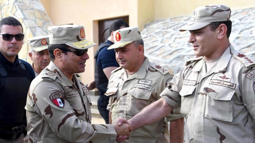 In this picture provided by the office of the Egyptian Presidency, Egyptian President Abdel-Fattah el-Sissi, second left, greets members of the Egyptian armed forces in Northern Sinai, Egypt, Saturday, July 4, 2015.  Egyptian President Abdel-Fattah el-Sissi has travelled to the troubled northern part of the Sinai Peninsula to inspect troops, after Islamic State-linked militants struck a deadly blow against the military this week in a coordinated assault. (Egyptian Presidency /Mohammed Abdel-Muati via AP)