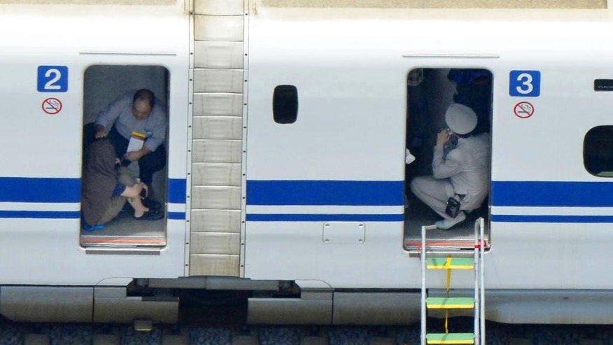 FILE- In this June 30, 2015 file photo, a passenger, left, crouches inside a train car of a bullet train which made an emergency stop after a man set himself on fire, in Odawara, west of Tokyo.  A fatal fire on Japan's bullet train, started by a man who self-immolated this week, has revealed surprising blind spots in a system renowned for its speed, punctuality and safety record. Experts say it was a wakeup call to something more disastrous, potentially terrorist attacks, and it's time to step up risk management ahead of the G-7 summit in Japan next year and the 2020 Tokyo Olympics. (Kyodo News via AP Photo, File) JAPAN OUT, MANDATORY CREDIT