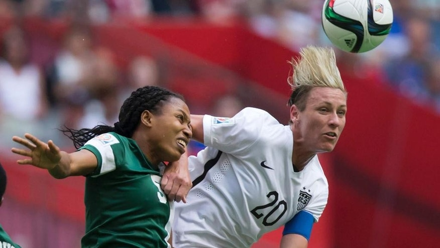 "FILE - In this June 16, 2015, file photo, Nigeria's Onome Ebi, left, and United States' Abby Wambach vie for the ball during a FIFA Women's World Cup soccer game in Vancouver, British Columbia, Canada. With the title match looming, Wambach isn't mincing words. ""All I care about is winning this World Cup,"" she said. The star U.S. forward is playing in her fourth Women's World Cup, and she says it will be her last. A victory Sunday, July 5, in the final against Japan would be the perfect ending to her World Cup career. (Darryl Dyck/The Canadian Press via AP, File)"
