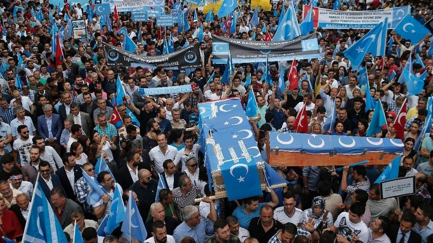 Uighurs living in Turkey and their supporters, some carrying coffins representing Uighurs who died in China's far-western Xinjiang Uighur region, chant slogans as they stage a protest in Istanbul, Saturday, July 4, 2015, against what they call as oppression by Chinese government to Muslim Uighurs in the province. Hundreds of people have marched in Istanbul to protest China over reports of its repression of its minority Muslim Uighur community. Turkey has ethnic and linguistic ties to the Uighurs, members of a Muslim ethnic minority in Xinjiang. Relations between China and Turkey have been strained over Turkish reports that Uighurs were banned from worshipping and fasting during the Muslim holy month of Ramadan.  (AP Photo/Emrah Gurel)