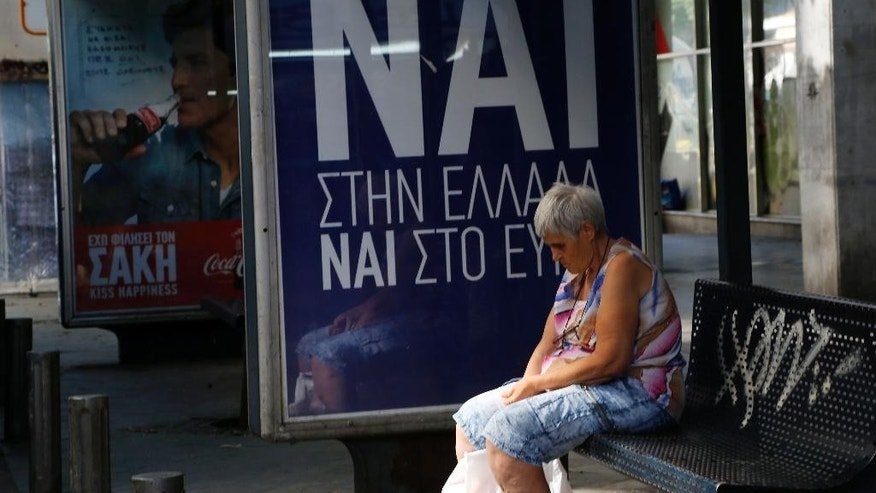 A woman waits at a bus stop net to a poster reading ''YES to Greece, yes to Euro'' referring to the Sunday referendum in Athens, Saturday, July 4, 2015. Whether Greeks decide in Sunday's referendum to accept their lenders' bailout deal or reject it, the government's hold on power may be shakier than its brash prime minister has calculated, analysts say. (AP Photo/Petros Karadjias)