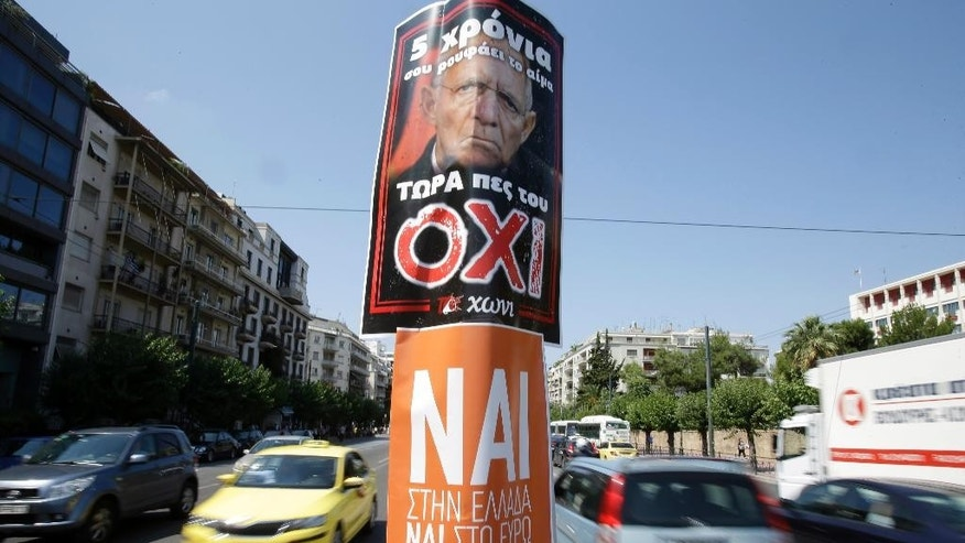 A woman searches a recycle bin as a poster depicting German Finance Minister Wolfgang Schaeuble reading ''For five years he is drinking your blood, now tell him NO'' referring to the upcoming referendum taking place on Sunday, in Athens, Saturday, July 4, 2015. Campaigns halted in Greece on Saturday on the eve of a closely watched bailout referendum — with voters in a dead heat over whether to defy creditors and push for better repayment terms or essentially seek new political leadership to find a compromise. (AP Photo/Petros Karadjias)