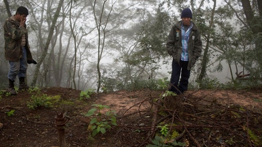 In this June 25, 2015 photo, Guarani environmental health specialist Albino Flores, right, and farmer David Benitez stand at the site of an unsealed oil well, left behind by the state-owned YPFB oil company inside Aguarague National Park in southeastern Bolivia. Benitez, who lives in the park and grazes his cattle among the wells, said the odor is much stronger in the summer, when theres no water to wash the oil downstream. (AP Photo/Juan Karita)