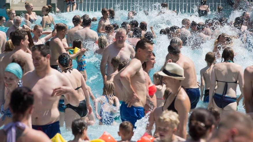 People cool off as they  enjoy refreshing in a public pool in Radebeul near Dresden, Saturday July 4, 2015.  From Spain to Poland, temperatures have climbed as a mass of hot air from Africa has pushed northward. Some cities have seen temperatures near or beyond 40 degrees Celsius (104 Fahrenheit), and they are expected to stay high through the weekend.  ( Sebastian Kahnert/dpa via AP)