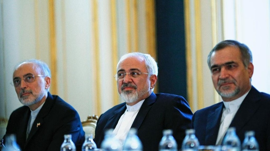 """Iranian Foreign Minister Mohammad Javad Zarif, centre, Head of the Iranian Atomic Energy Organization Ali Akbar Salehi, left, and Hossein Fereydoon, brother and close aide to President Hassan Rouhani, meet with U.S. Secretary of State John Kerry in Vienna, Austria, Friday July 3, 2015.  Iran has committed to implementing the IAEA's """"additional protocol"""" for inspections and monitoring as part of an accord, but the rules don't guarantee international monitors can enter any facility including sensitive military sites, so making it difficult to investigate allegations of secret work on nuclear weapons. (Carlos Barria/Pool via AP)"""