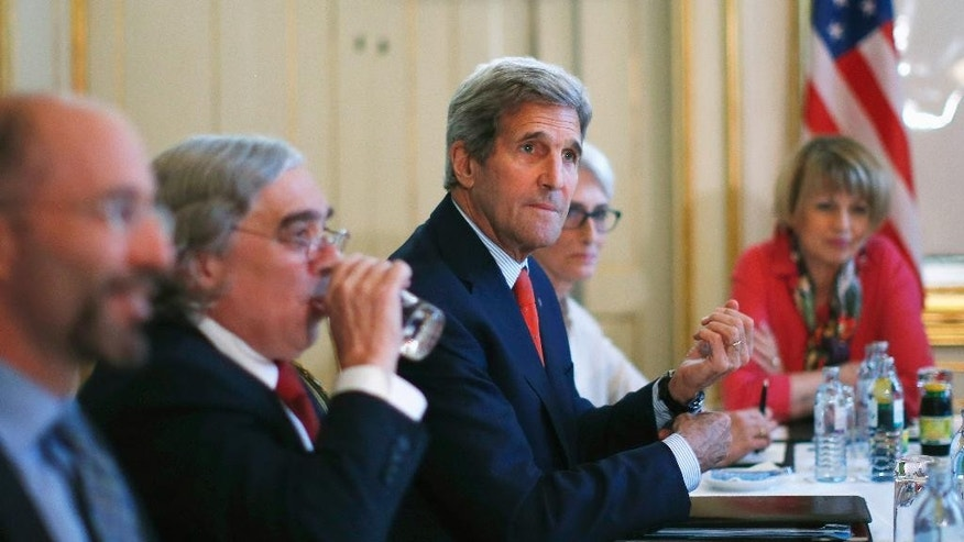 """U.S. Secretary of State John Kerry, centre, meets with Iranian Foreign Minister Mohammad Javad Zarif in Vienna, Austria, Friday July 3, 2015.  Iran has committed to implementing the IAEA's """"additional protocol"""" for inspections and monitoring as part of an accord, but the rules don't guarantee international monitors can enter any facility including sensitive military sites, so making it difficult to investigate allegations of secret work on nuclear weapons. (Carlos Barria/Pool via AP)"""