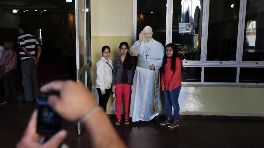 In this June 7, 2015 photo, tourists take pictures with a life-size cutout poster of Pope Francis after attending Mass celebrating the feast day of Corpus Cristi at the Basilica of the Virgin of Caacupe in Caacupe, Paraguay. On July 11, Francis will celebrate Mass in the square in front of this basilica, in part to accommodate the hundreds of thousands of people expected to attend. (AP Photo/Jorge Saenz)