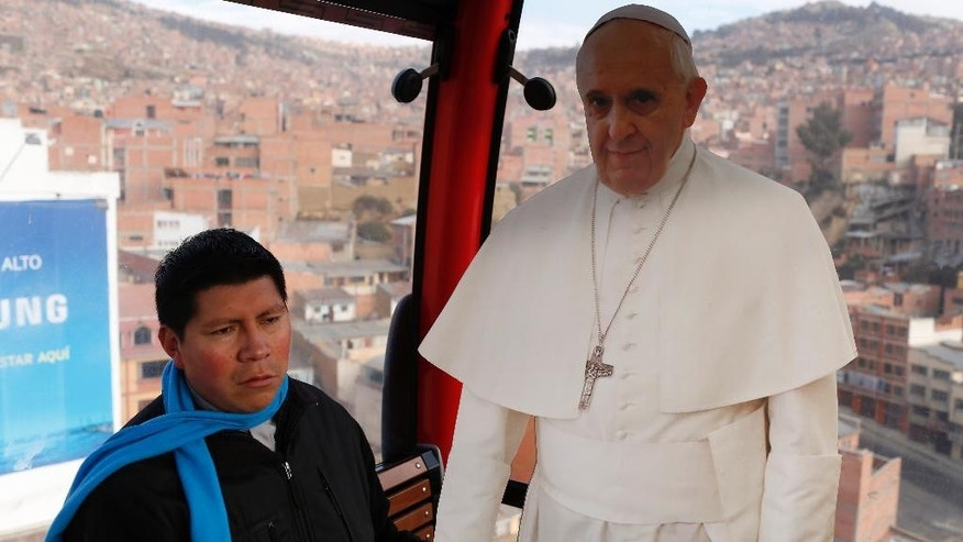 Catholic Priest Ivan Bravo rides with a life-size cutout poster of Pope Francis in a cable car that links downtown La Paz with El Alto, as a way to promote the pope's upcoming visit to Bolivia, Friday, July 3, 2015. Pope Francis' trip to South America that includes Bolivia is set for July 5-12, though he will only spend four hours in Bolivia's capital due to the altitude, church officials say. (AP Photo/Juan Karita)