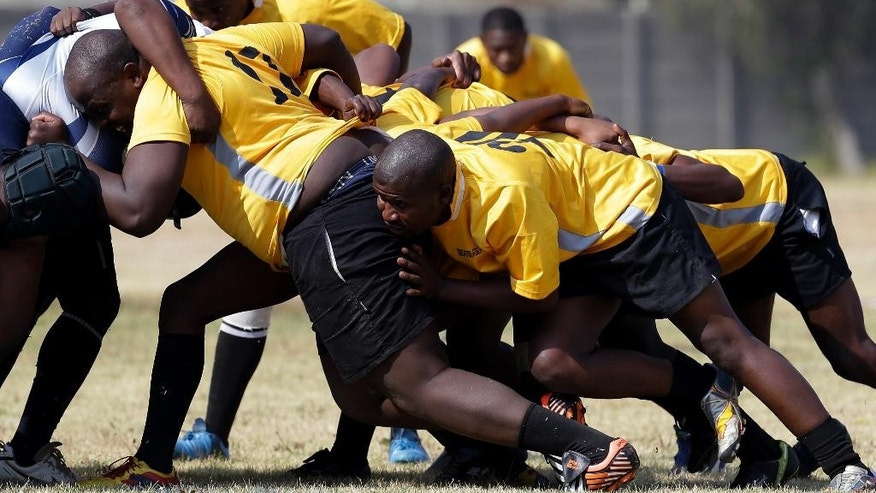 In this photo taken on Saturday, May 23, 2015, Kanyiso Sopitshi, left, with teammates scrum during their league match in Springs east of Johannesburg, South Africa. Their catches still uncertain, their sneakers worn and unsuitable, a team of young South Africans is trying to find success in a sport that that's a traditional favorite in their country, but rare in their own neighborhood - rugby.(AP Photo/Themba Hadebe)