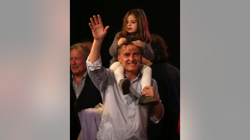 Carrying his daughter Antonia and surrounded by supporters, the current Mayor of Buenos Aires and presidential candidate Mauricio Macri celebrates at the end of mayoral elections in Buenos Aires, Argentina, Sunday, July 5, 2015. Buenos Aires will have a runoff election that would have the current Cabinet Chief of Buenos Aires and mayoral candidate Horacio Rodriguez Larreta competing against Martín Lousteau, candidate of the ECO coalition. (AP Photo/Daniel Jayo)