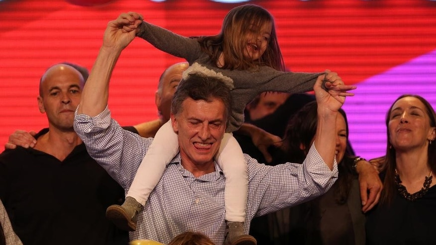 Carrying his daughter Antonia, surrounded by supporters, the current Mayor of Buenos Aires and presidential candidate Mauricio Macri celebrates at the end of mayoral elections in Buenos Aires, Argentina, Sunday, July 5, 2015. Buenos Aires will have a runoff election that would have the current Cabinet Chief of Buenos Aires and mayoral candidate Horacio Rodriguez Larreta competing against Martín Lousteau, candidate of the ECO coalition. (AP Photo/Daniel Jayo)