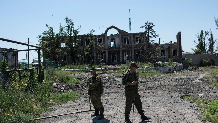 Russia-backed fighters check the territory for mines during an OSCE patrol in Shyrokyne, Donetsk region eastern Ukraine, Saturday, July 4, 2015. (AP Photo)