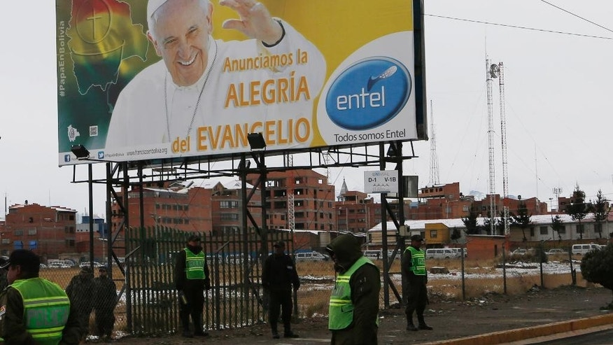 "Police stand guard near a billboard of Pope Francis covered by the Spanish words: ""With Francis. We announce the joy of the Gospel"" as they train ahead of his arrival in El Alto, Bolivia, Saturday, July 4, 2015. The pope's trip to South America that includes Bolivia is set for July 5-12, though he will only spend four hours in Bolivia due to the altitude, church officials say. (AP Photo/Juan Karita)"