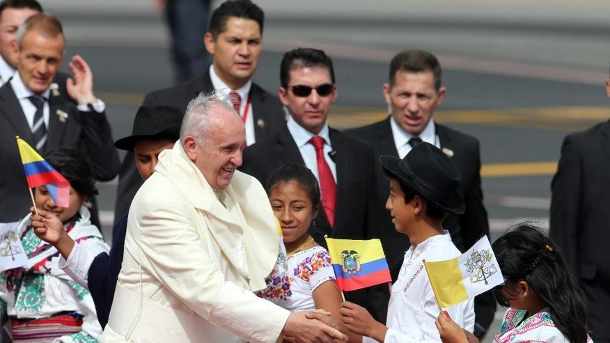Pope Francis greets several children upon his arrival to the Mariscal Sucre International airport in Quito Sunday July 5, 2015. History's first Latin American pope returns to Spanish-speaking South America for the first time on Sunday to visit Ecuador, Bolivia and Paraguay.(AP Photo/