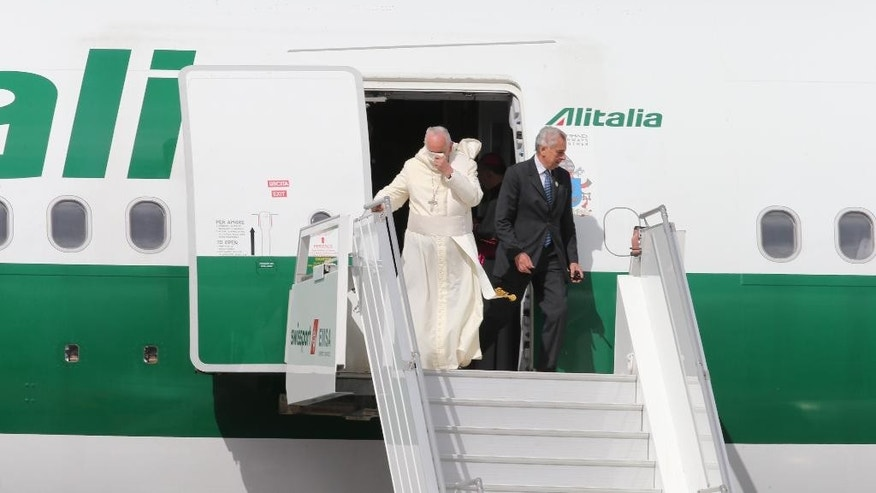 Pope Francis disembarks from his plane upon his arrival to the Mariscal Sucre International airport in Quito Sunday July 5, 2015. History's first Latin American pope returns to Spanish-speaking South America for the first time on Sunday to visit Ecuador, Bolivia and Paraguay. (AP Photo/Fernando Llano)