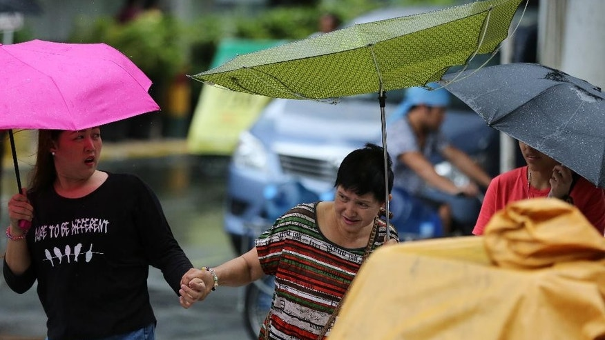 Filipinos hold on while strong winds blow an umbrella upside down as Tropical Storm Linfa enhanced the southwest monsoon in Manila, Philippines on Sunday, July 5, 2015. Tropical Storm Linfa blew across northern Philippines, causing floods and knocking out power in several towns in provinces. (AP Photo/Aaron Favila)