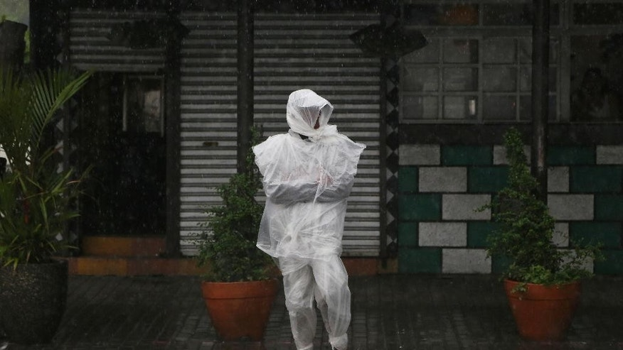 Filipino Efren Villamor, 62, wears plastic sheets to shield him from rain as Tropical Storm Linfa enhanced the southwest monsoon in Manila, Philippines on Sunday, July 5, 2015. Tropical Storm Linfa blew across northern Philippines, causing floods and knocking out power in several towns in provinces. (AP Photo/Aaron Favila)
