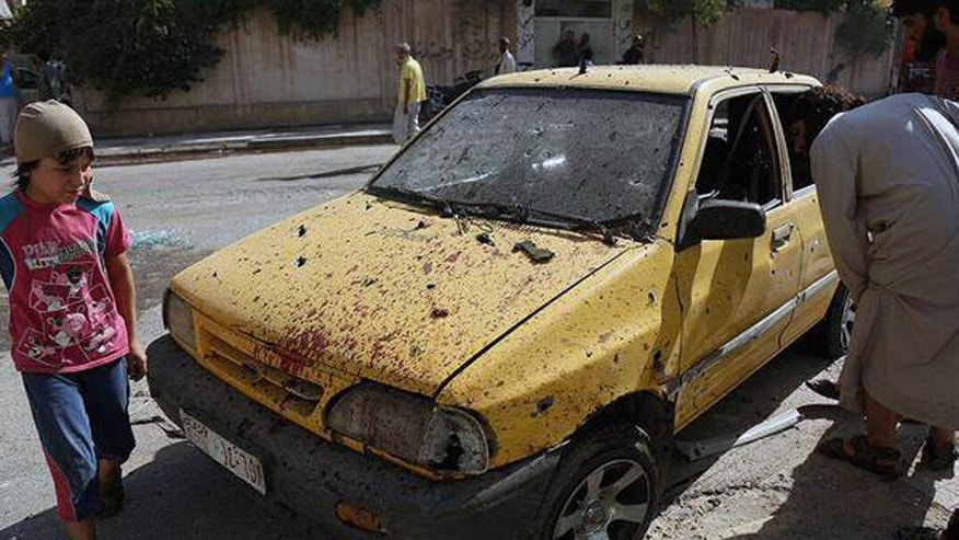"This Saturday, July, 4, 2015 photo provided by a website of the Islamic State group, shows people inspecting a car purportedly damaged by U.S.-led airstrikes on Raqqa, Syria. A series of U.S.-led coalition airstrikes targeting the Islamic State group's stronghold of Raqqa in eastern Syria has killed at least 10 militants and wounded many others. The airstrikes were confirmed by the coalition, Raqqa-base activists and the Islamic State group. Arabic on banner reads, ""Raqqa Urgent / Ten killed and tens wounded by crusader (Christian)-Nusayri (Alawite) coalition on Raqqa city. 17 Ramadan 1436 Hijri."" (Islamic State militant website via AP)"