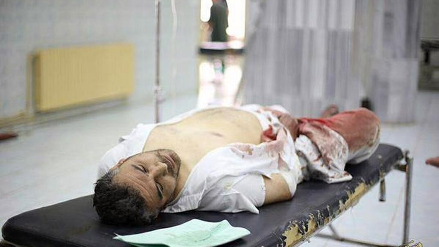 "This Saturday, July, 4, 2015 photo provided by a website of the Islamic State group, shows a wounded man on a stretcher in Raqqa, Syria. A series of U.S.-led coalition airstrikes targeting the Islamic State group's stronghold of Raqqa in eastern Syria has killed at least 10 militants and wounded many others. The airstrikes were confirmed by the coalition, Raqqa-base activists and the Islamic State group. Arabic on banner reads, ""Raqqa Urgent / Ten killed and tens wounded by crusader (Christian)-Nusayri (Alawite) coalition on Raqqa city. 17 Ramadan 1436 Hijri."" (Islamic State militant website via AP)"