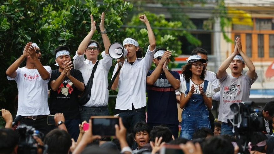 """In this June 24, 2015 photo, student activists gather outside Pathumwan Police Station in Bangkok, Thailand. Fourteen detained student activists went before a military court in Thailand on Tuesday, July 7, 2015 in a case that has attracted international calls for their release and criticism of the military junta's strict controls on freedom of speech and assembly. The university students were arrested June 26 on charges of sedition and violating the junta's ban on political gatherings for leading a peaceful anti-coup rally in Bangkok. Their head bands read """"return the power."""" (AP Photo/Sakchai Lalit)"""