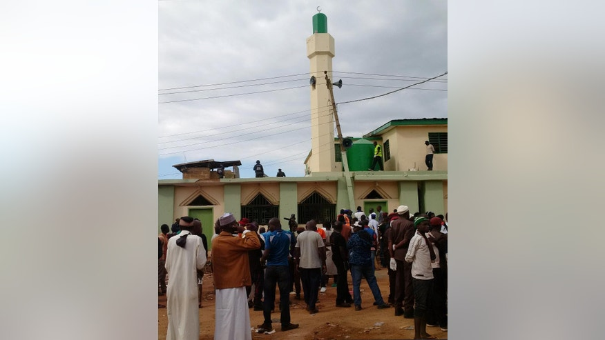 In this photo taken on a mobile phone, people gather near a mosque where a bomb exploded earlier in Jos, Nigeria, Monday, July 6, 2015. Two bombs blamed on the Islamic extremist group Boko Haram exploded at a crowded mosque and a Muslim restaurant in Nigeria's central city of Jos, killing 51 people, officials said Monday. (AP Photo)