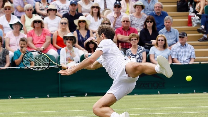 Richard Gasquet of France leaps for a shot during his singles match against Nick Kyrgios of Australia, at the All England Lawn Tennis Championships in Wimbledon, London, Monday July 6, 2015. (AP Photo/Kirsty Wigglesworth)