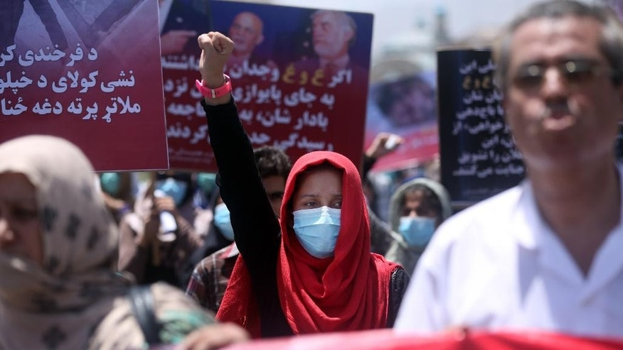 A woman chants slogans during a protest held by the Solidarity Party of Afghanistan for 27 year-old Farkhunda, who was beaten to death by a mob months ago, at the site of the attack in Kabul, Monday, July 6, 2015. More than one hundred gathered to demand justice for the woman who was killed on March 19 outside one of the capital's most famous mosques. (AP Photo/Massoud Hossaini)