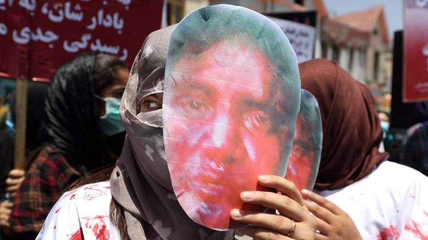 Women wear masks that bear pictures of  27 year-old Farkhunda, who was beaten to death by a mob months ago, during a protest held by the Solidarity Party of Afghanistan at the site of the attack in Kabul, Monday, July 6, 2015. More than one hundred gathered to demand justice for the woman who was killed on March 19 outside one of the capital's most famous mosques. (AP Photo/Rahmat Gul)