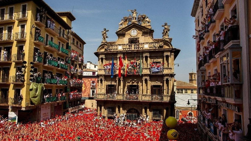 "Revelers hold up traditional red neckties during the launch of the ""Chupinazo"" rocket, to celebrate the official opening of the 2015 San Fermin fiestas in Pamplona, Spain, Monday, July 6, 2015. Revelers from around the world turned out here to kick off the festival with a messy party in the Pamplona town square, one day before the first of eight days of the running of the bulls. (AP Photo/Andres Kudacki)"