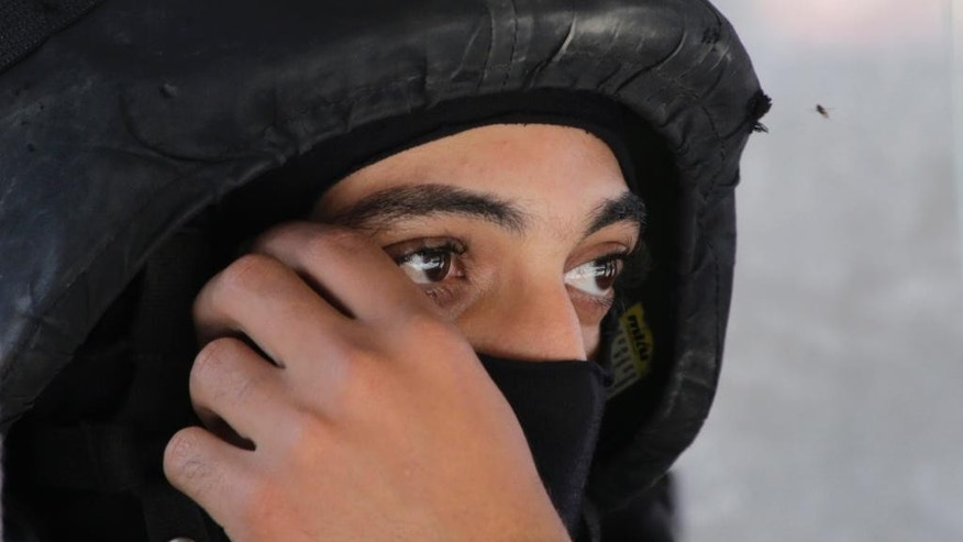 FILE - In this Tuesday, June 30, 2015 file photo, an Egyptian special forces soldier covers his face as he secures a convoy carrying Egypt's slain Prosecutor General Hisham Barakat before to his funeral in Cairo, Egypt. After a series of stunning militant attacks, including the assassination of the country's top prosecutor Barakat, the government is pushing through a new controversial anti-terrorism draft bill. (AP Photo/Amr Nabil, File)