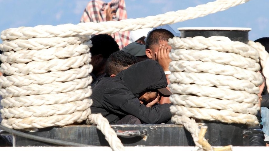 Migrants wait to be disembarked from the Italian Navy ship Dattilo, at the Reggio Calabria harbor, Southern Italy, Thursday, July 2, 2015. The number of migrants crossing the Mediterranean to southern Europe was more than 80 percent higher in the first half of 2015 than a year earlier, with deaths initially soaring before dropping back as rescue efforts at sea were stepped up, the U.N. refugee agency said Wednesday. (AP Photo/Adriana Sapone)