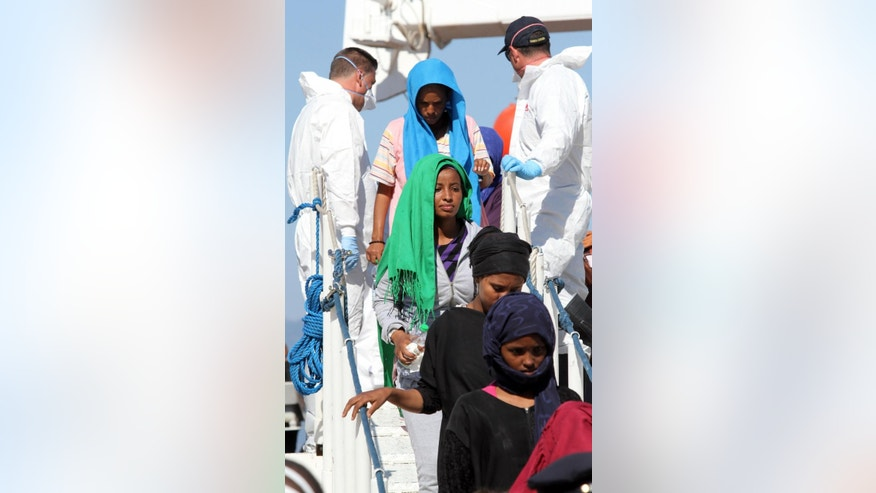 Migrants disembark from the Italian Navy ship Dattilo, at the Reggio Calabria harbor, Southern Italy, Thursday, July 2, 2015. The number of migrants crossing the Mediterranean to southern Europe was more than 80 percent higher in the first half of 2015 than a year earlier, with deaths initially soaring before dropping back as rescue efforts at sea were stepped up, the U.N. refugee agency said Wednesday. (AP Photo/Adriana Sapone)
