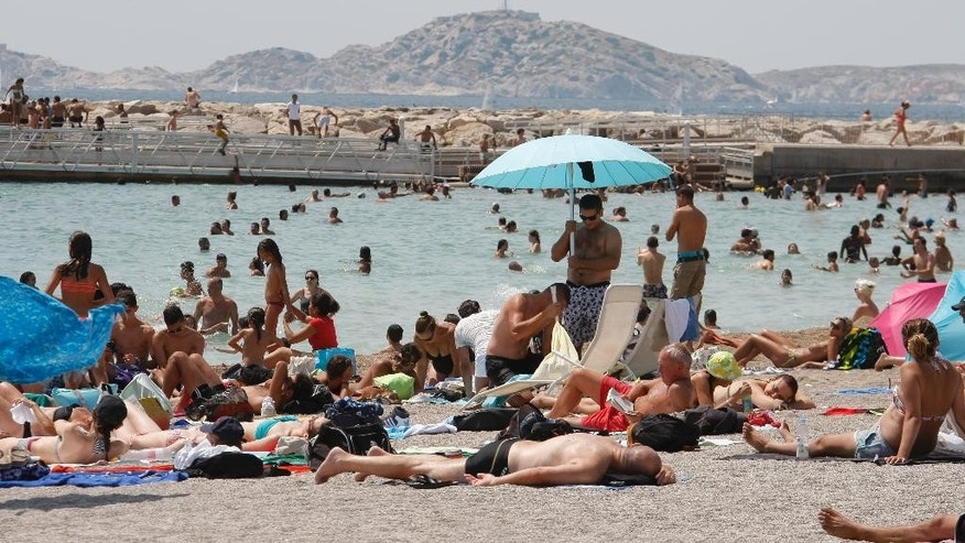 People sunbathe at Prado beach, in Marseille, southern France, Sunday July 5, 2015. A mass of hot air moving north from Africa is bringing unusually hot weather to Western Europe, with France in recent days experiencing temperatures around 34 degrees Celsius (93 Fahrenheit). (AP Photo/Claude Paris)