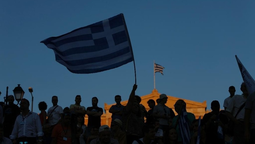 """Supporters of the No vote wave Greek flags after the referendum's exit polls at Syntagma square in Athens, Sunday, July 5, 2015. Greece faced an uncharted future as officials counted the results of a referendum Sunday on whether to accept creditors' demands for more austerity in exchange for rescue loans, with three opinion polls showing a tight race with a narrow victory likely for the """"no"""" side. (AP Photo/Emilio Morenatti)"""
