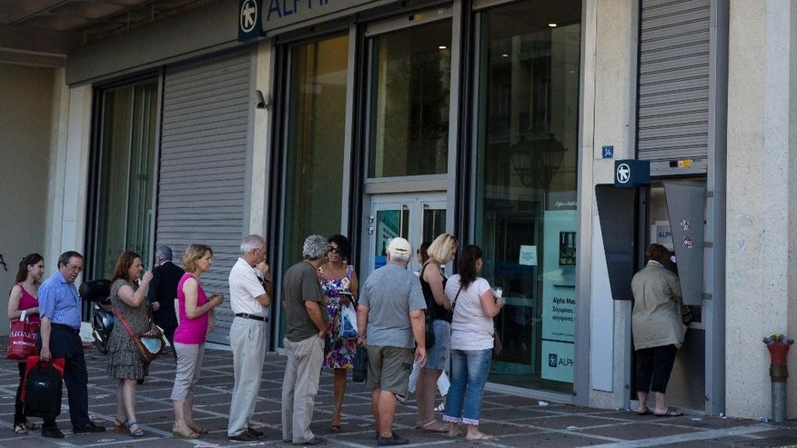 "People line up to use an ATM machine outside a bank in Athens, on Monday, July 6, 2015. Greece's Finance Minister Yanis Varoufakis has resigned following Sunday's referendum in which the majority of voters said ""no"" to more austerity measures in exchange for another financial bailout. (AP Photo/Petros Giannakouris)"