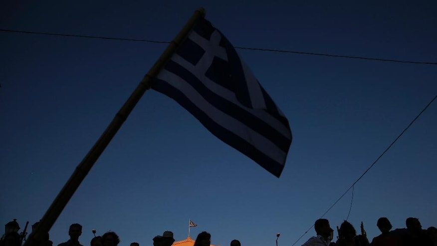 Supporters of the No vote wave Greek flags after the results of the referendum at Syntagma square in Athens, Sunday, July 5, 2015. Greeks overwhelmingly rejected creditors' demands for more austerity in return for rescue loans in a critical referendum Sunday, backing Prime Minister Alexis Tsipras, who insisted the vote would give him a stronger hand to reach a better deal. (AP Photo/Petros Giannakouris)