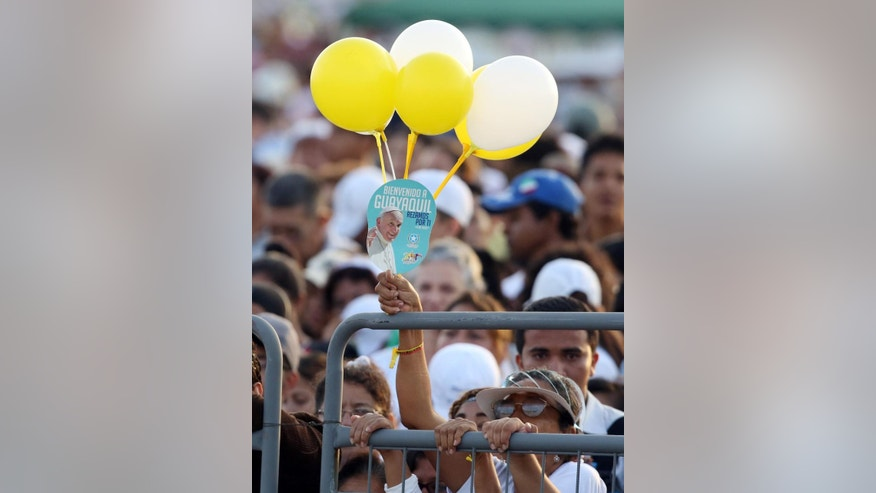 "A woman holds a balloon bouquet in Vatican colors and a placard with an image of Pope Francis with a message that reads in Spanish; ""Welcome to Guayaquil, We pray for you,"" as she waits for the arrival of Francis to celebrate a Mass at the Samanes Park in Guayaquil, Ecuador, Monday, July 6, 2015.  Hours before Francis arrives in Ecuador's port city of Guayaquil, thousands are already waiting in Samanes where the pope is expected to celebrate Mass with up to 1 million people. (AP Photo/Fernando Vergara)"