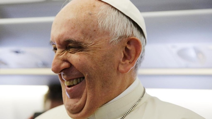 Pope Francis laughs as he meets the journalists aboard the papal airplane on the occasion of his visit to Quito, Ecuador, July 5, 2015. The Pontiff is visiting Ecuador, Bolivia and Paraguay during his Apostolic trip from July 5 to July 12. (AP Photo/Gregorio Borgia)