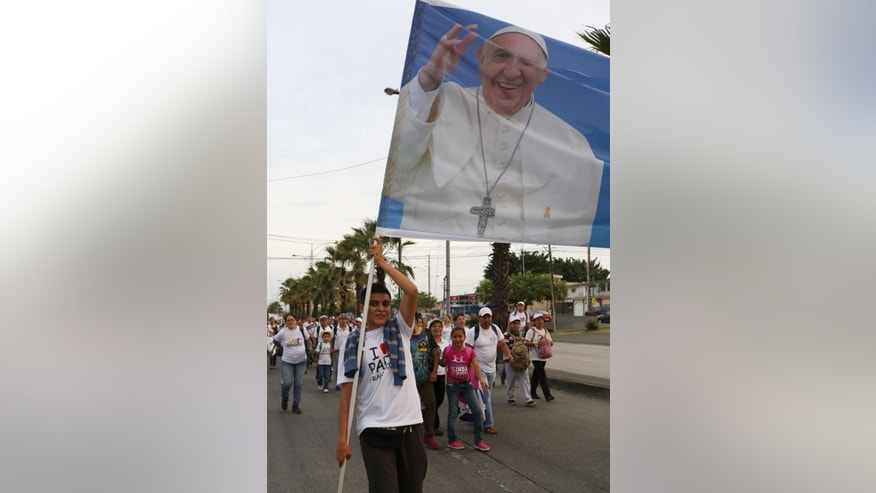 A man holds a banner of Pope Francis as he walks toward Samanes Park where Pope Francis will offer a mass, to take part in a vigil in Guayaquil, Ecuador, Sunday, July 5, 2015. Francis is making his first visit as pope to his Spanish-speaking neighborhood. He'll travel to three South American nations, Ecuador, Bolivia and Paraguay, which are beset by problems that concern him deeply, income inequality and environmental degradation. (AP Photo/Fernando Vergara)