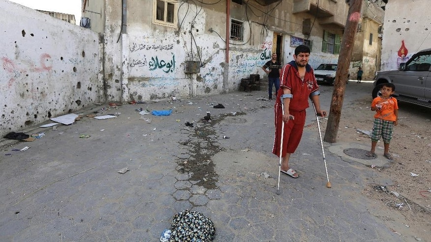 In this Saturday, June 27, 2015 photo, Mohammed al-Selek, 39, shows the site where he was injured by an Israeli mortar strike in front of his family house, during an interview with The Associated Press, in the Shijaiyah neighborhood of Gaza City, northern Gaza Strip. Al-Selek's life changed forever last July 30, when Israeli mortar shells slammed into his home  killing all his three children, his father and six other relatives. A year later, al-Selek, who lost his leg during the airstrike, still struggles to recover and come to terms with his family's loss in the 50-day Israel-Hamas war. (AP Photo/Adel Hana)